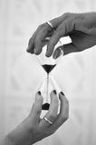 Hourglass of love. Marriage is the passage of time together, an hourglass of love where her hand supports her hand by tackling time together Royalty Free Stock Image