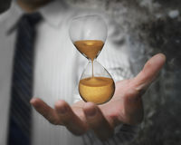 Hourglass in the man's hand Royalty Free Stock Image