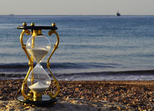 Hourglass on marine beach. Symbolizing a short time of vacation Stock Photos