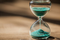 An hourglass measuring the passing time in a countdown to a deadline. Sand running through the bulbs of an hourglass measuring the passing time in a countdown to stock image