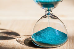 An hourglass measuring the passing time in a countdown to a deadline. Sand running through the bulbs of an hourglass measuring the passing time in a countdown to Royalty Free Stock Photography