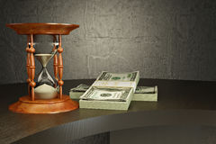 Hourglass and money on the desk. Royalty Free Stock Photo