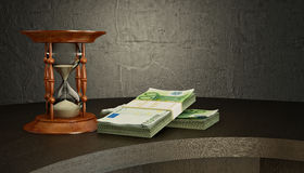 Hourglass and money on the desk Royalty Free Stock Photos