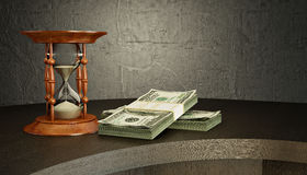Hourglass and money on the desk Stock Photography