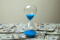 Hourglass and money dollars banknotes royalty free stock photography