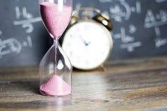 Hourglass na drewnie z blackboard tłem Obraz Royalty Free