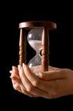 Hourglass nas mãos em um preto foto de stock royalty free