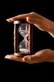 Hourglass nas mãos em um preto foto de stock