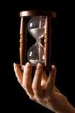 Hourglass nas mãos em um preto fotos de stock