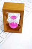 Hourglass and notebook computers Royalty Free Stock Photo