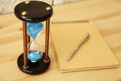 Hourglass and notebook on wooden table. Time management concept stock image