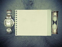 Hourglass notepad and watch lying on the table retro style Stock Photo