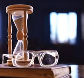 Hourglass, old book and eyeglasses on wooden table, dark background. Sand falling down inside of hourglass. Time flow. Concept. Wooden hourglass counting time Royalty Free Stock Photo