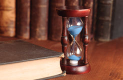 Hourglass And Old Books Stock Photo