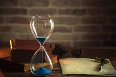 Hourglass and old books with old paper and pen. stock image