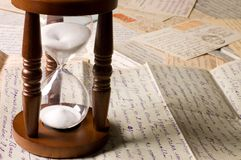 Hourglass on old letters Royalty Free Stock Image