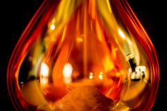 An hourglass of an orange color on black background royalty free stock photography