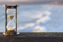 Hourglass Outdoors with Ocean Background. Hourglass Outdoors - sunlit hourglass or sand timer with a background of flowing water stock photography