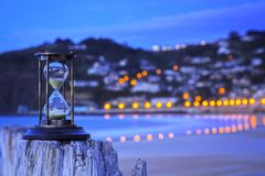Hourglass Outdoors and Street Lights. Hourglass on an old post at a beach, overlooking distant town and street lights stock photo