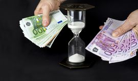 Hourglass and paper money. Time is money concept.  stock photography