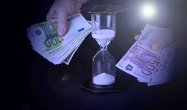 Hourglass and paper money. Time is money concept.  stock image