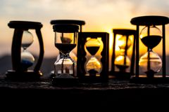 Hourglass Passing of Time Lapse Clouds. An hourglass in front of a bright blue sky with puffy white clouds passing. Time concept. Sunset time. Selective focus royalty free stock images