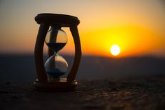Hourglass Passing of Time Lapse Clouds. An hourglass in front of a bright blue sky with puffy white clouds passing. Time concept. Sunset time. Selective focus royalty free stock image