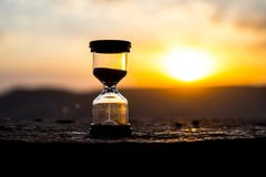 Hourglass Passing of Time Lapse Clouds. An hourglass in front of a bright blue sky with puffy white clouds passing. Time concept. Sunset time. Selective focus royalty free stock photos