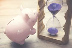 Hourglass with piggy bank. On wooden table Royalty Free Stock Image