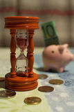 Hourglass and piggy bank - Time is money. Hour glass with coins around and piggy bank with bank note inside in the background - Metaphor `Time is money Royalty Free Stock Images
