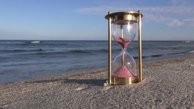 Hourglass with pink sand by the sea