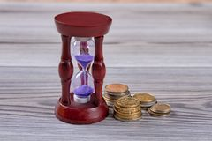 Hourglass with purple sand. Columns of coins on wood, close up stock photos