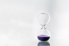Hourglass. And purple sand on gray background stock image
