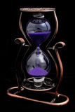 Hourglass with purple sand in a metal frame Stock Image