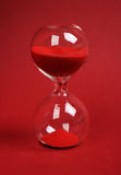 Hourglass on red background. Vertical Royalty Free Stock Image