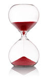 Hourglass with red sand running through Royalty Free Stock Photos