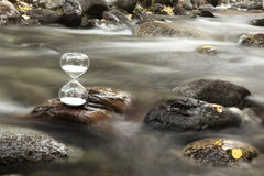A hourglass on a rock of a creek. stock image