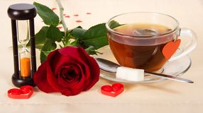 Hourglass, rose and cup of tea Stock Image