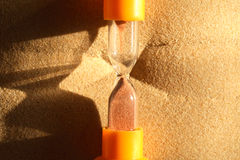 Hourglass On Sand. Time concept. Closeup of hourglass on abstract sand background with free space for text Stock Images