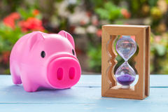 Hourglass or sand clock on wood and pigbank. Hourglass or sand clock on wood and pig bank on wood royalty free stock image