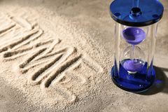 Hourglass on sand. Time management concept royalty free stock image