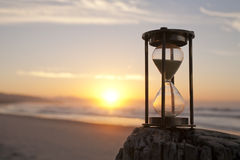Hourglass Sand Timer Beach Sunrise. An hourglass on a beach in front of a beautiful sunrise, shallow DOF Royalty Free Stock Photography