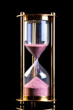 Hourglass sand timer on black Stock Images