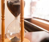 Hourglass, sandglass. Closeup of  hourglass or sandglass on wooden table in backlight Stock Photos