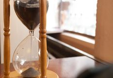 Hourglass, sandglass. Closeup of  hourglass or sandglass on wooden table in backlight Stock Photo