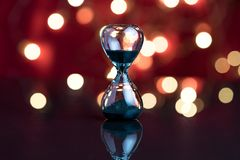 Hourglass or sandglass on red dark background with decoration li. Ght bokeh using as Party always end concept Royalty Free Stock Photography