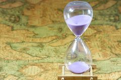 Hourglass, sandglass, sand timer, sand clock on old treasure world map Stock Photo