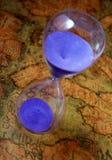 Hourglass, sandglass, sand timer, sand clock on old treasure world map Royalty Free Stock Photos