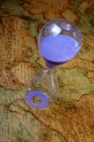 Hourglass, sandglass, sand timer, sand clock on old treasure world map Stock Images