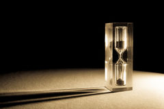 Hourglass sandglass  with shadows and glare of the sun on a dark background. Old retro style vintage photo. Royalty Free Stock Photos